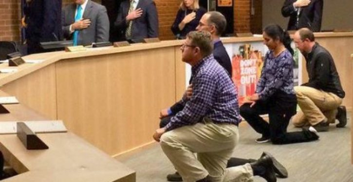 Four Ann Arbor city council members take a knee during Pledge of Allegiance