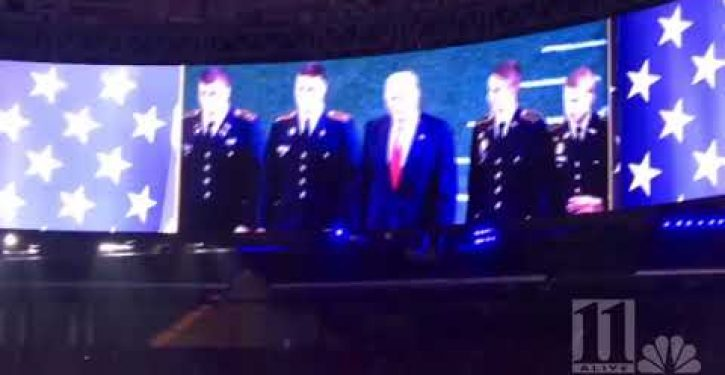 While Trump stood for the national anthem, he received a crude larger-than-life message