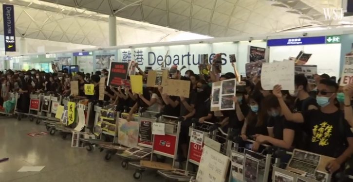 Police, protesters clash at Hong Kong airport; China moves military forces near border