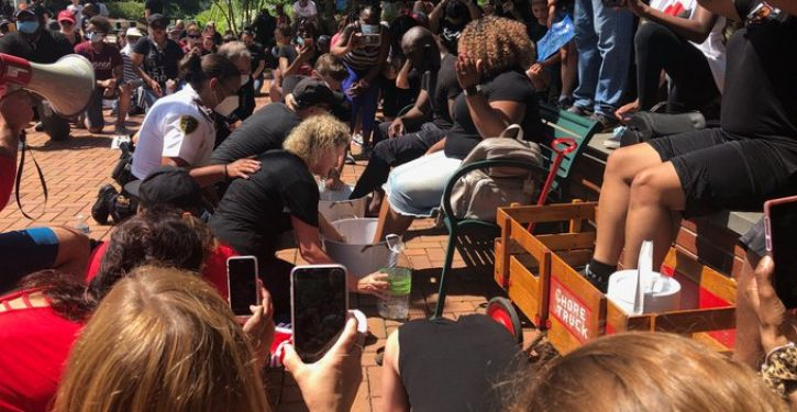 It's come to this: 'Guilty' whites, including cops, kneel, wash feet of black community leaders